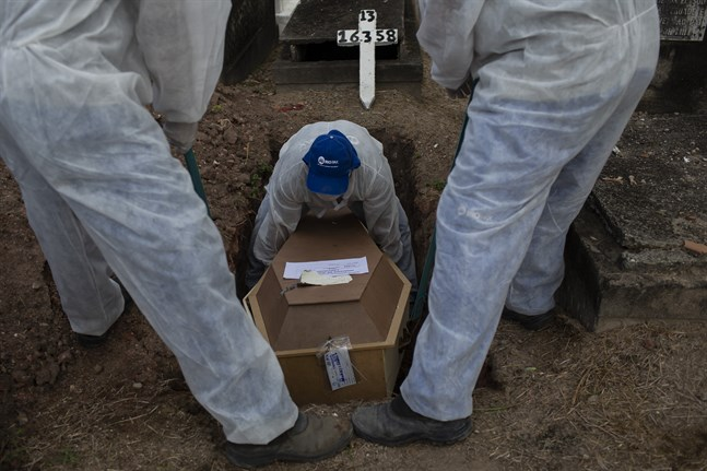 Begravningsarbetare på en kyrkogård i Rio de Janeiro arbetar iförda skyddsdräkter. Bild från tidigare i veckan.