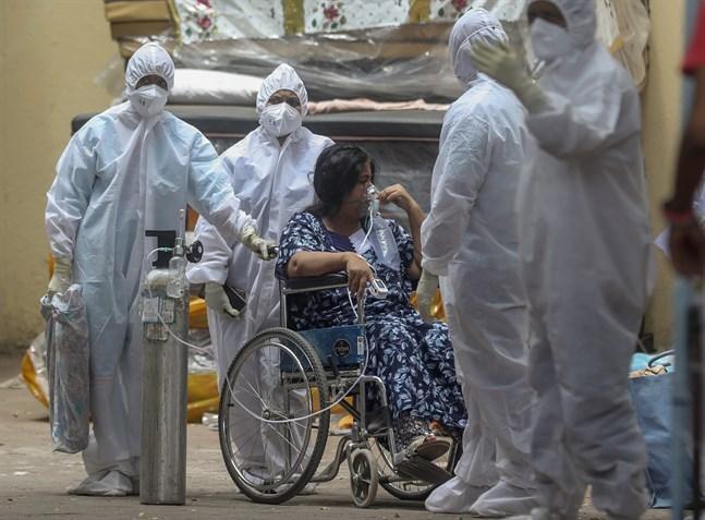Vårdpersonal tar hand om en covidpatient i Bombay i Indien – där pandemin skenar utom kontroll.