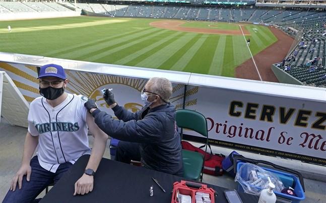 Den avtagande vaccinationstakten i USA oroar, men här får Seattle Mariners-supportern Hunter Moreira sitt covidvaccin före basebollmatchen mot Baltimore Orioles.