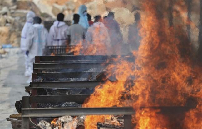 En begravning pågår i bakgrunden, krematorieeld i förgrunden på denna bild från Bengaluru i Indien.