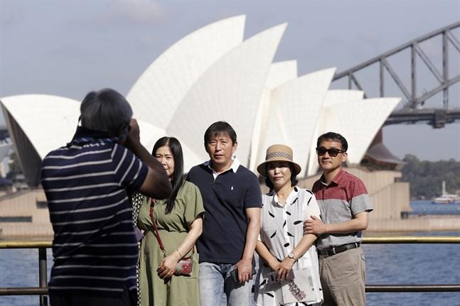 Turister låter fotografera sig framför Sydneys berömda operahus, i januari 2020, innan Australiens gränser stängdes. Internationella turister kommer troligen inte att kunna besöka landet förrän tidigast i mitten av 2022.