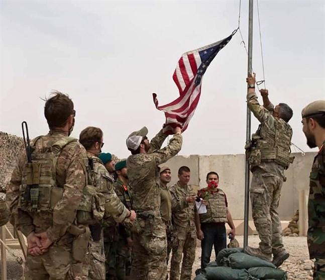 Den amerikanska flaggan halas i samband med att den amerikanska armén lämnar över en militärbas till den afghanska armén i provinsen Helmand, söndagen den 2 maj.