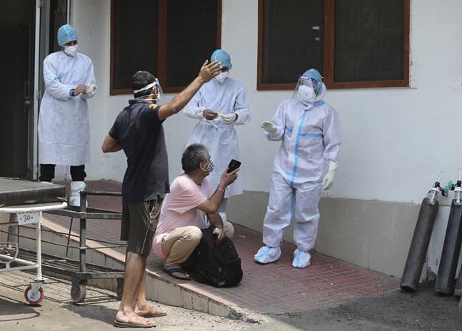 En covidsjuk man talar med vårdpersonal utanför ett sjukhus i Jammu i Indien.