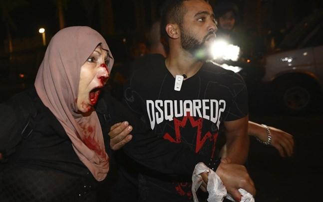 En skadad palestinsk demonstrant tas om hand i området Sheik Jarrah i östra Jerusalem.