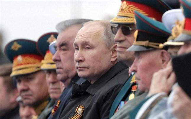 Rysslands president Vladimir Putin har sällskap av ett antal dignitärer då han ser på paraden på Röda torget i Moskva.