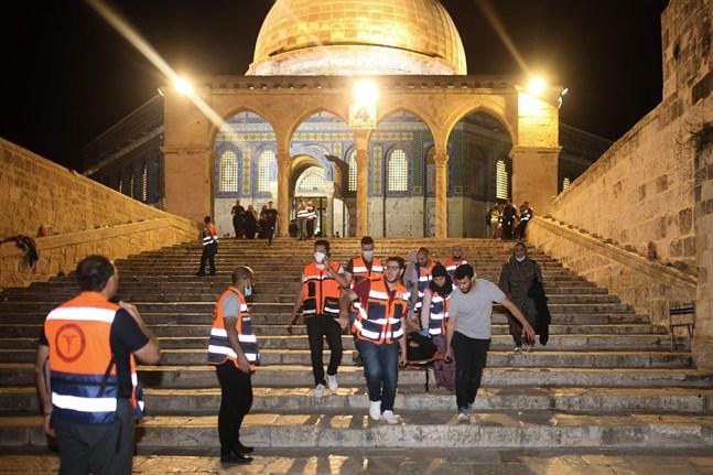 Palestinska vårdare evakuerar en person som skadats under en sammandrabbning mellan israelisk polis och palestinska demonstranter i Jerusalem. Läget i Jerusalem är det värsta på flera år.