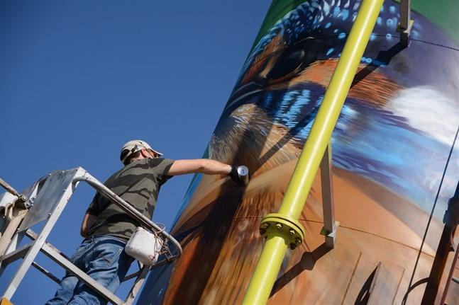 Domenico Frodo i full färd med att måla kungsfiskaren som ska pryda vattenverkets silo i Malax.
