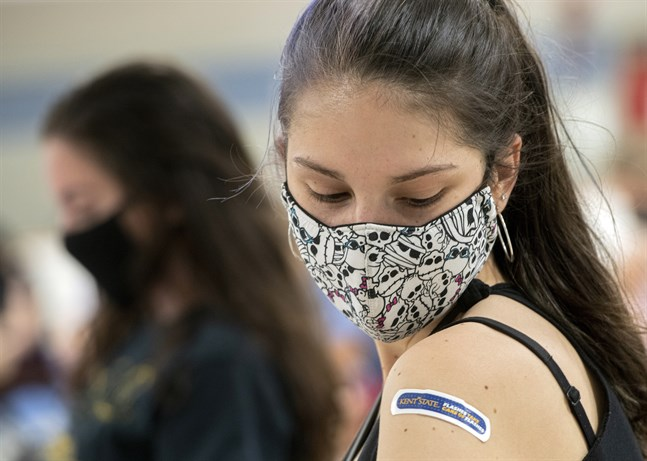 Regan Raeth, student vid Kent State University, tittar på sitt plåster efter att ha vaccinerats i Ohio. Bild från i april.