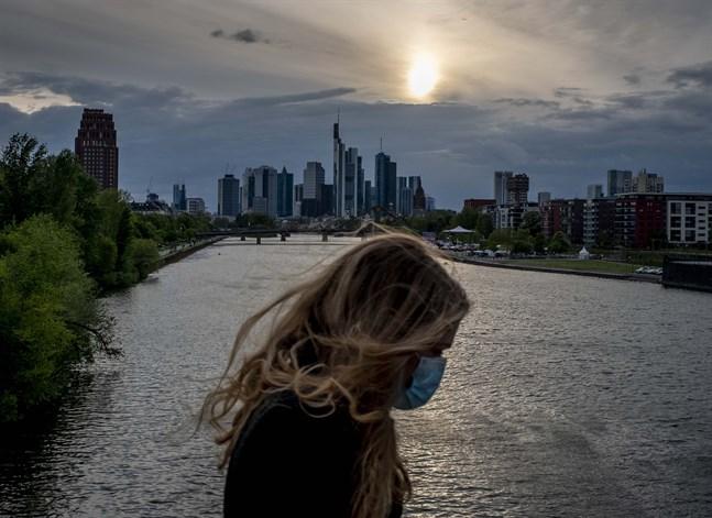 En kvinna med munskydd på en bro över floden Main i Frankfurt. Bilden är från i torsdags.