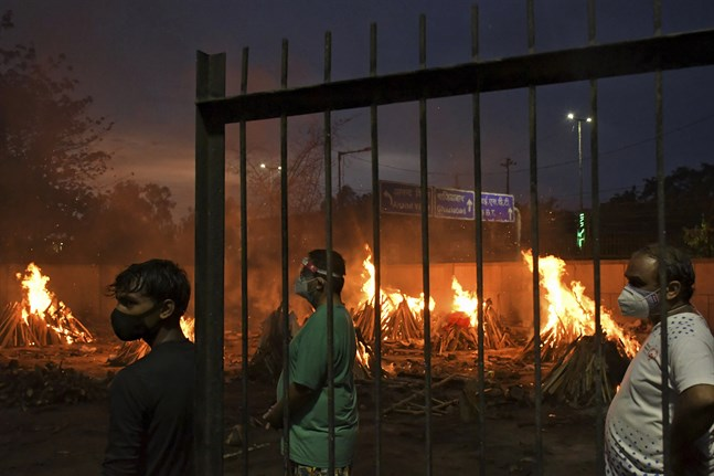 Många indier som avlidit med covid-19 dumpas i Indiens stora vattendrag. Här säger människor farväl till sina anhöriga vid ett provisoriskt krematorium i huvudstaden New Delhi den 6 maj. Arkivbild.