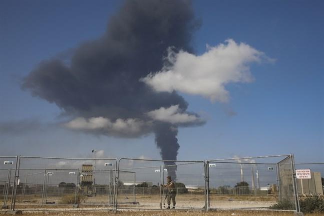 En israelisk soldat framför en rökplym från en oljetank som träffats av raketer från Gaza. Bilden är från tidigare i veckan.