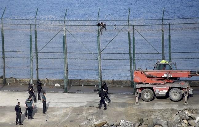 Många migranter försöker ta sig in i Ceuta genom att klättra över stängslet vid gränsen. Andra simmar. Arkivbild.