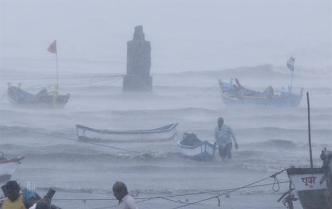 Fiskare vid kusten utanför Bombay försöker säkra sina båtar inför cyklonen Tauktae.