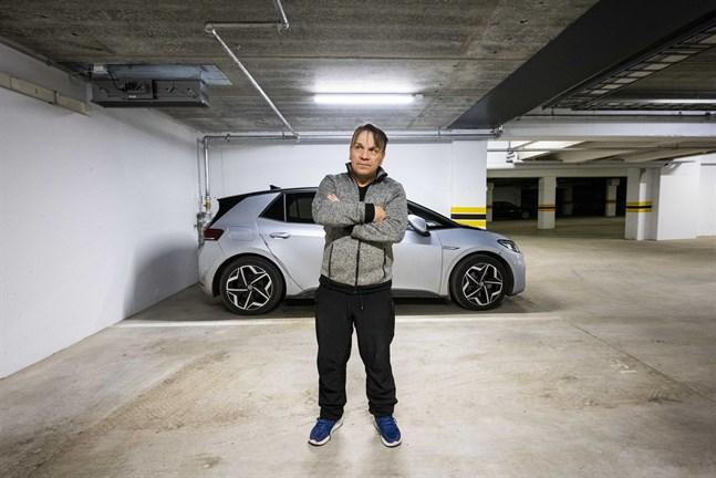 Kari Ojanen med sin elbil i bakgrunden. Men här, i p-grottan under den nya bostaden, blir det ingen laddning för hans del. Det blir helt enkelt för dyrt.