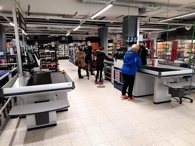Kassakön ringlade lång då den nya matbutiken öppnade i före detta Halpa-Hallihuset på torsdagen. Karin Westergård betalar sitt inköp i kassan.