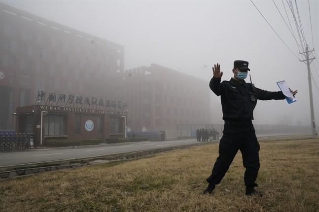 En säkerhetsvakt motar bort journalister från det laboratorium i Wuhan, där sars-cov2-viruset uppstod enligt vissa teorier. Arkivbild.