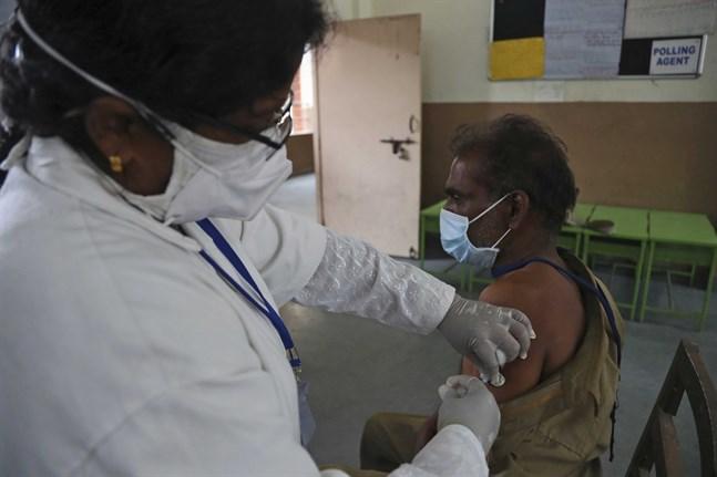 En man får vaccin i indiska Hyderabad. Över 220 miljoner doser vaccin har getts i landet som har en befolkning på omkring 1,4 miljarder människor.
