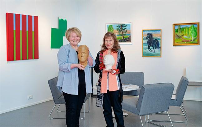 Varsin skulptur föreställande ett huvud har Ann-Britt Kronqvist och Irmeli Räsänen tagit med sig till sin utställning i Galleri Bruno. På väggarna bakom dem syns några av deras tavlor.