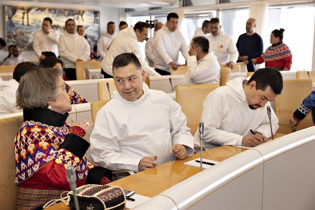 Medlemmar i det grönländska parlamentet inatsisartut under ett möte i april i år. I mitten av bilden sitter Pele Broberg som nu riktar kritik mot Danmarks försvarspaket.