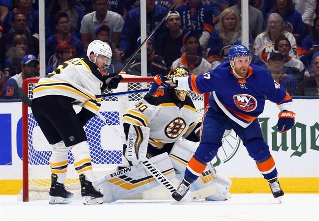 """New York Islanders Leo Komarov (till höger) skymmer sikten för Bostonkeepern Tuukka Rask samtidigt som han tappat klubban under """"blusen"""" på motståndaren Mike Reilly."""