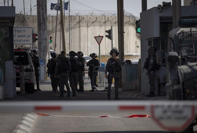 Israeliska soldater samlas vid den vägspärr mellan Jerusalem och Ramallah i Västbanken, där en kvinna sköts till döds efter att hon knivbeväpnad närmat sig gränsvakterna.