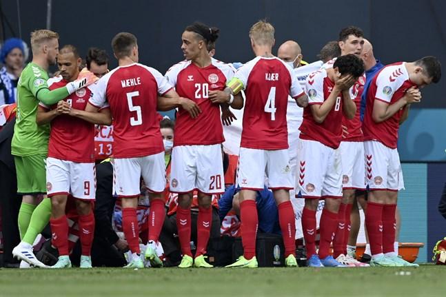 De danska spelarna bildade en mur runt Christian Eriksen när han fick behandling på planen i Köpenhamn.