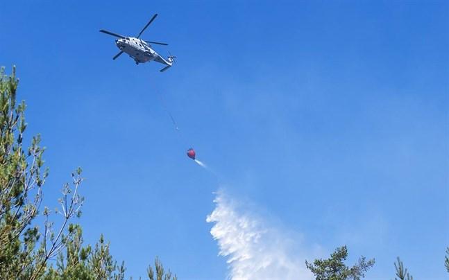 En skogsbrand rasar norr om Mora. Bland annat deltar två helikoptrar i släckningsarbetet. Bilden är tagen när en helikopter vattenbombar en skogsbrand vid ett annat tillfälle.