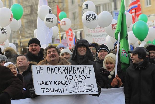 Författaren Dmitrij Bykov håller en skylt under en protest i Moskva 2012. Bredvid står oppositionsledaren Aleksej Navalnyj.