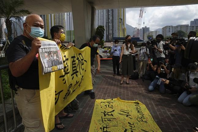 Demonstranter protesterar på lördagen utanför domstolen i Hongkong, till stöd för två chefer vid den prodemokratiska tidningen Apple Daily som ställs inför rädda.