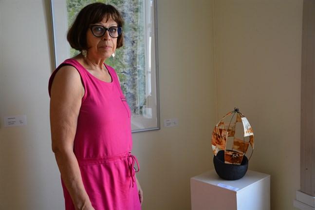 Kaija Porkala visar sitt arbete i keramik och grafik på tyg. I bakgrunden ses Pirkko Ogawas målning.