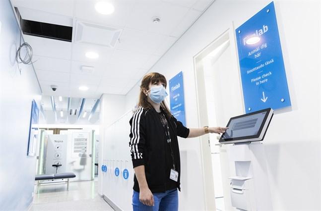 Daniela Utriainen-Agengo visar var kunderna börjar sitt besök i Fimlabs nya laboratorium – vid anmälningsautomaterna.