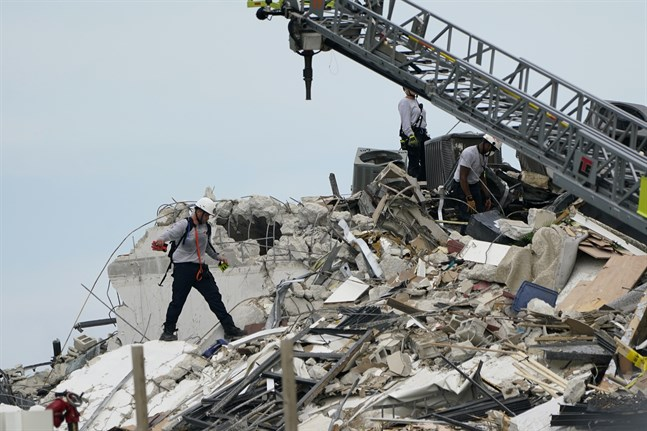 Räddningsarbetare vid det raserade huset.