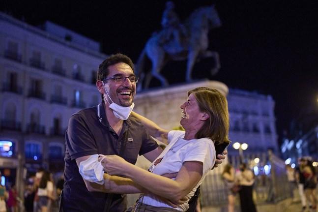 Ett par firar vid torget Puerta del Sol i Madrid efter det att munskyddskravet slopats vid midnatt, natten till den 26 juni.