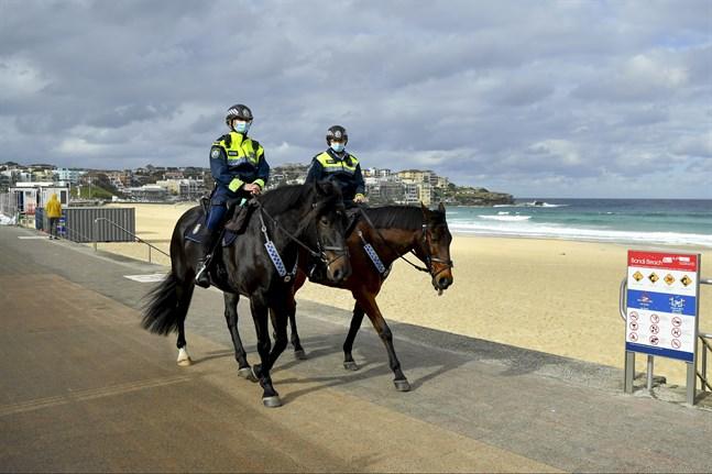 Poliser patrullerar Bondi Beach i Sydney för att se till att alla följer nedstängningen.