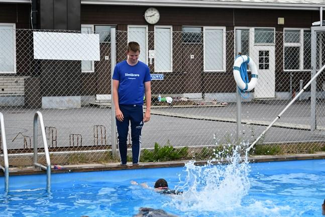 Simlektionen är i full gång och deltagarna leker en lek där de ska simma över till andra sidan av bassängen på olika sätt.