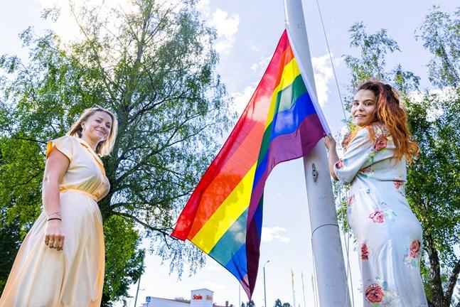 Isabel Flemming och Linn Nyholm hissar prideflaggan vid Övermalax uf.