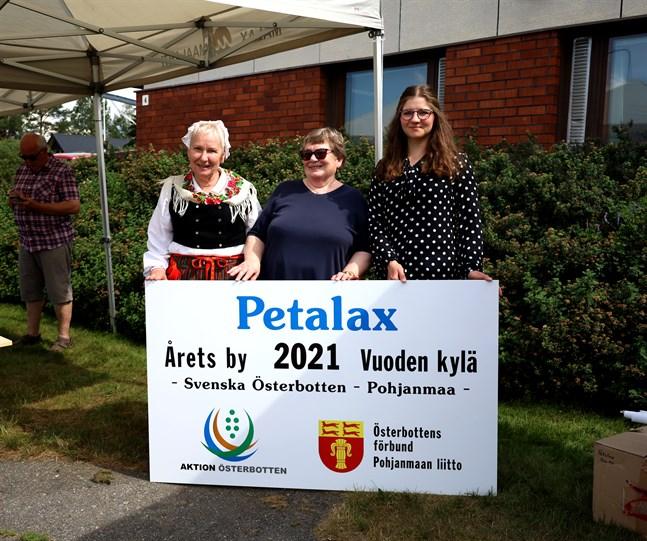 Petalax hembygdsförening ordförande Kerstin Knip till vänster. Kristina Vesterback i mitten är aktiv inom föreningen Arbetsgruppen för Petalax. Till vänster står Frida Lähdesmäki som är byaombud i Aktion Österbotten. Alla tre håller upp skylten som kommer att placeras på Strandvägen.