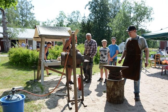 Eskil Grahn förevisar smide för Anders Greggas med barnbarnen Levi och Hugo Senkas, samt för Per-Erik Hellman som står skymd bakom ässjan.