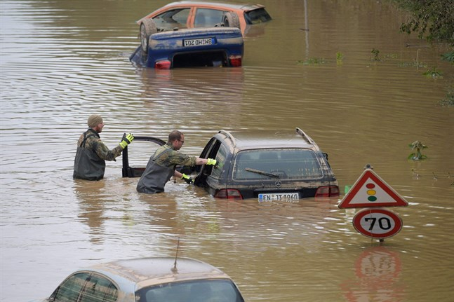 Inkallade styrkor söker efter offer bland översvämmade bilar i Erfstadt i västra Tyskland. Bilden togs i lördags.