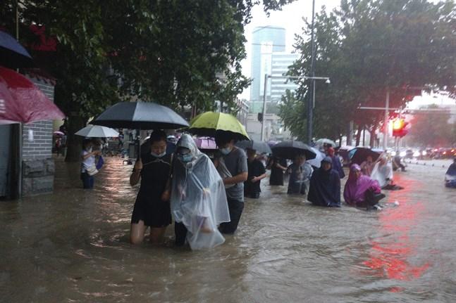 Invånare i Zhengzhou flyr de översvämmade gatorna.