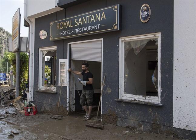 En man står framför sin restaurang som förstörts i översvämningarna i Altenahr, Tyskland.