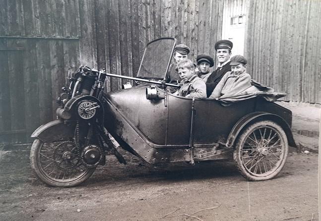 """Viktor Myhrmans trehjuliga phänomobil 1912? En stolt ägare och fyra glada pojkar. Men, vilka är de? Vet någon? Framhjulsdrivet ekipage med sparkstyrning. Tvåcylindrig fyrtaktsmotor med kedjedrift och fläktkylning av de öppna cylindrarna. Gasbelysning. Kan ej ha varit lätt att framföra på den tidens """"hästvägar"""". Bilen gjorde ju tre hjulspår! Notera den utanpåliggande handbromsspaken."""