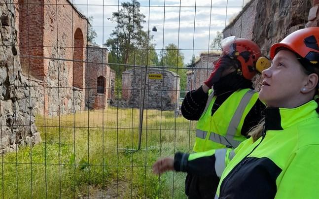 Eija Saukkoriipi, längst fram, och Pauliina Koivunen inspekterar området på muren där väder och vind har tryckt ut stenar, vilket utgör en säkerhetsrisk.