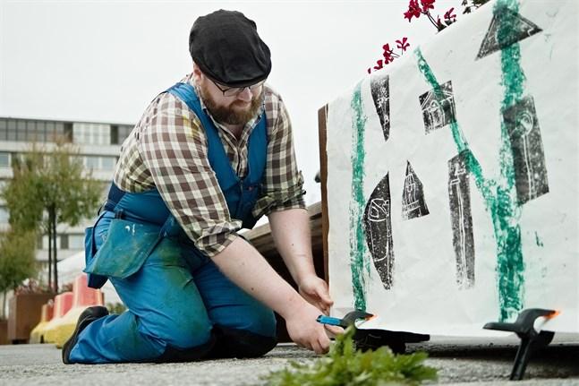 Jakobstads sommarkonstnär Johan Sandås är här i full färd med att hänga sitt offentliga verk på torget i Jakobstad. Han konstaterar att det blir en väldigt tillfällig utställning.