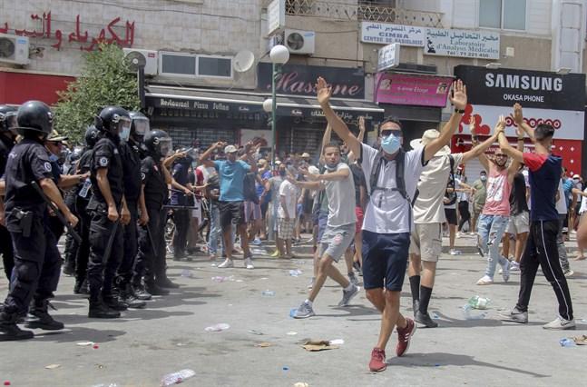Demonstranter och polis i Tunis på söndagen.