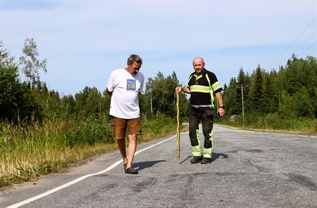 Henrik Backlund och Göran Burman står vid gropen som sträcker sig över körfältet.