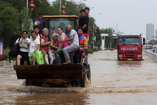Människor räddas undan översvämningarna i Henan i Kina.