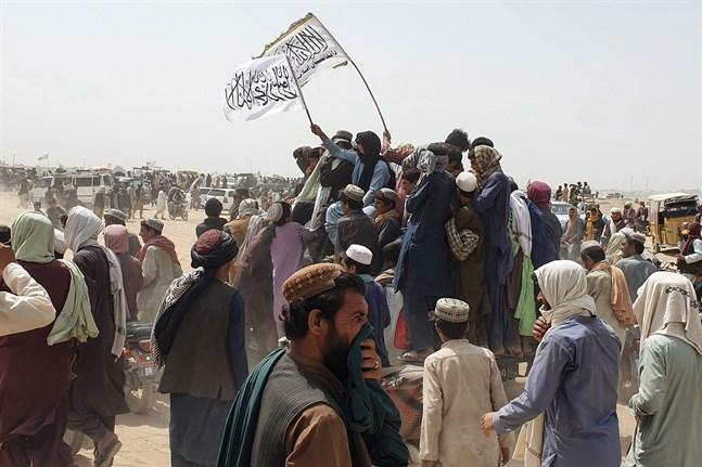 Människor viftar med talibanernas flagga medan de kör genom staden Chaman vid den pakistanska gränsen till Afghanistan 14 juli 2021.