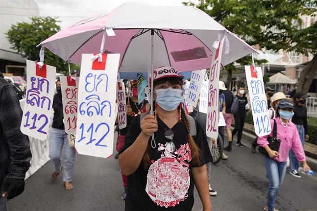 """En prodemokratisk demonstrant bär skyltar med texten """"nej till artikel 112"""", den avdelning av Thailands brottsbalk som handlar om majestätsbrott."""