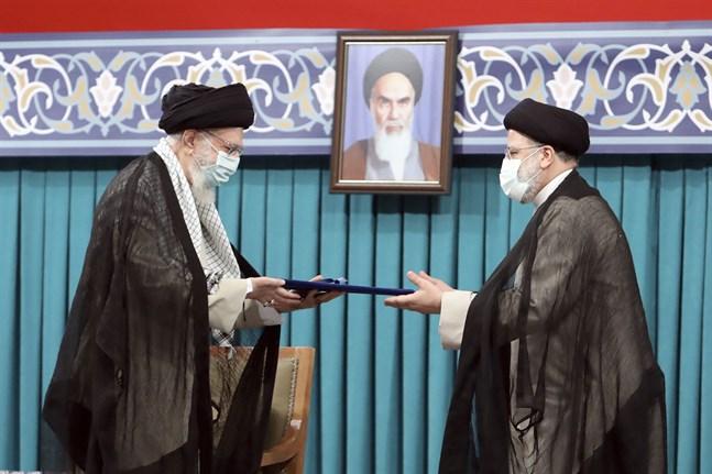 Irans högsta ledare Ayatollah Ali Khamenei (till vänster) ger sitt officiella godkännande till landets nya president Ebrahim Raisi vid en ceremoni i huvudstaden Teheran.